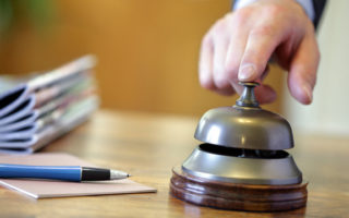 Businessman ringing a hotel reception service bell to attract attention
